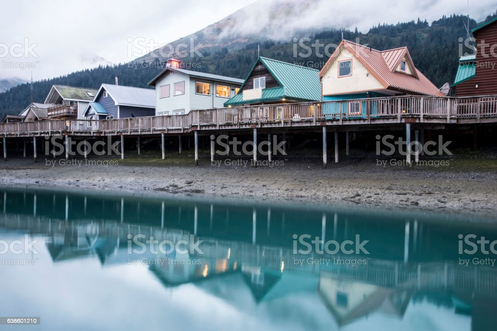 Colorful houses beneath fog and above water in Seward, Alaska. stock photo