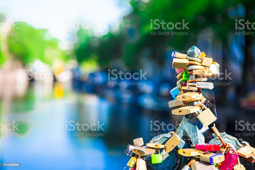 Colorful hundreds of padlocks-love locks on canal in Amsterdam, Netherlands stock photo