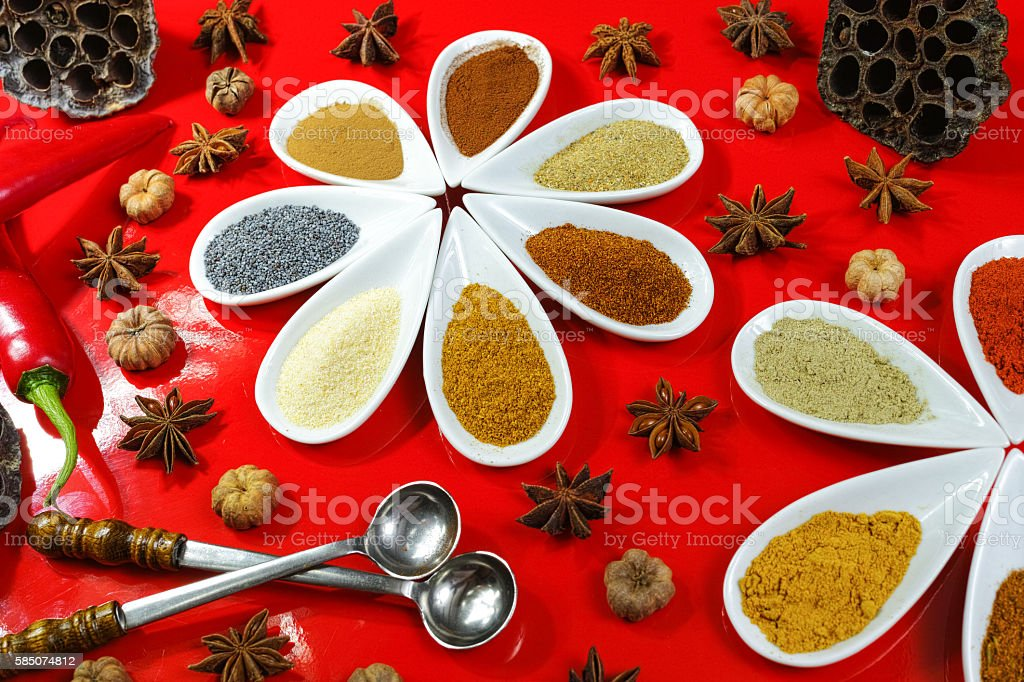 Colorful Indian spices on red background stock photo