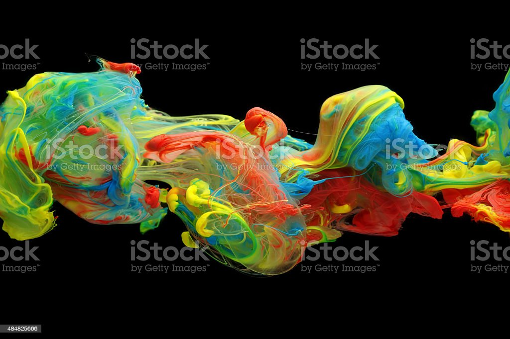 Colorful ink and paint swirling through water stock photo