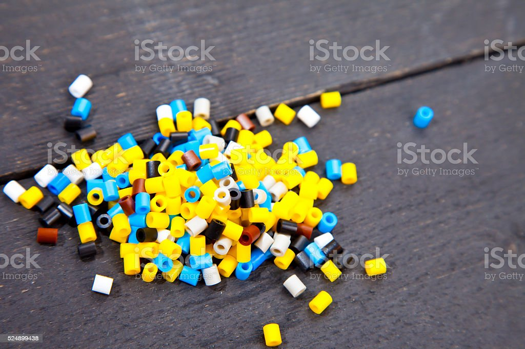 Colorful iron beads on dark black wooden background stock photo