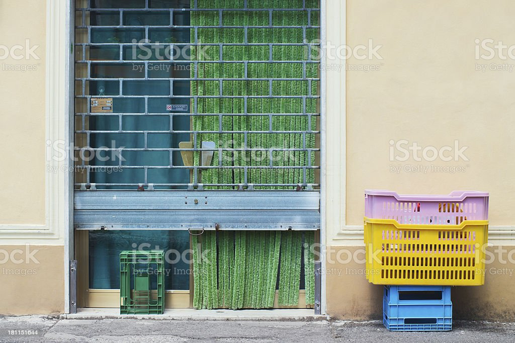 Colorful Italian small shop front - steel rolling shutter stock photo