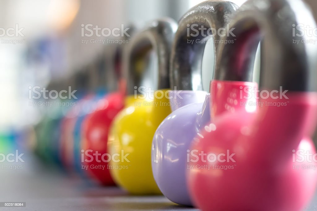 colorful kettlebells lining on table stock photo