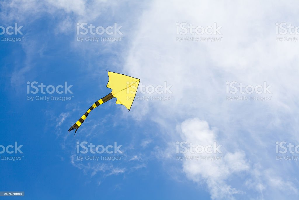 Colorful kite flying in the cloudy sky. copy space stock photo