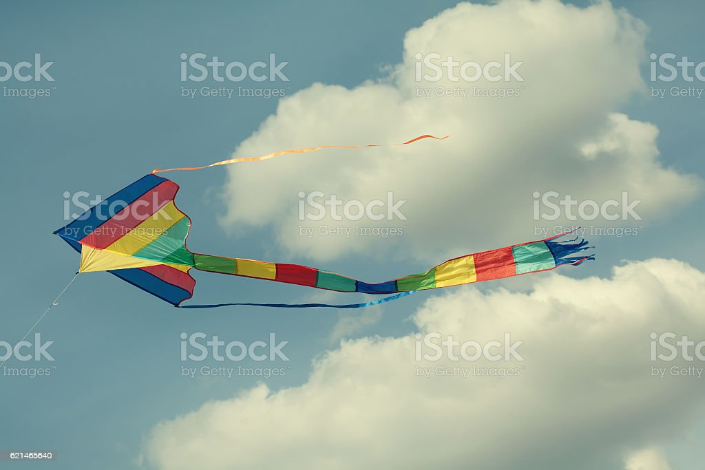 Colorful kite flying in the cloudy sky. stock photo
