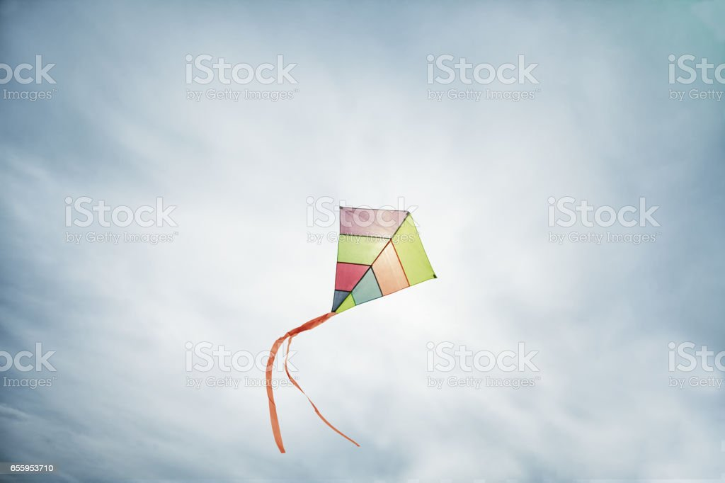 colorful kite flying with waving red bow stock photo