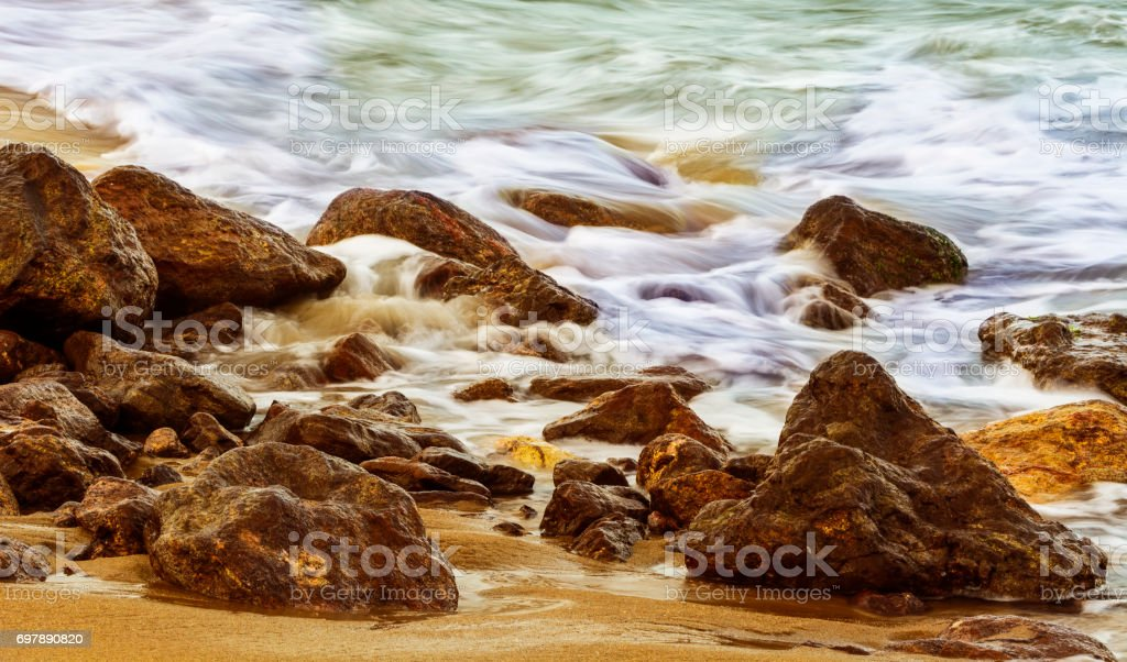 Colorful long exposure of the sea over rocks and sand stock photo