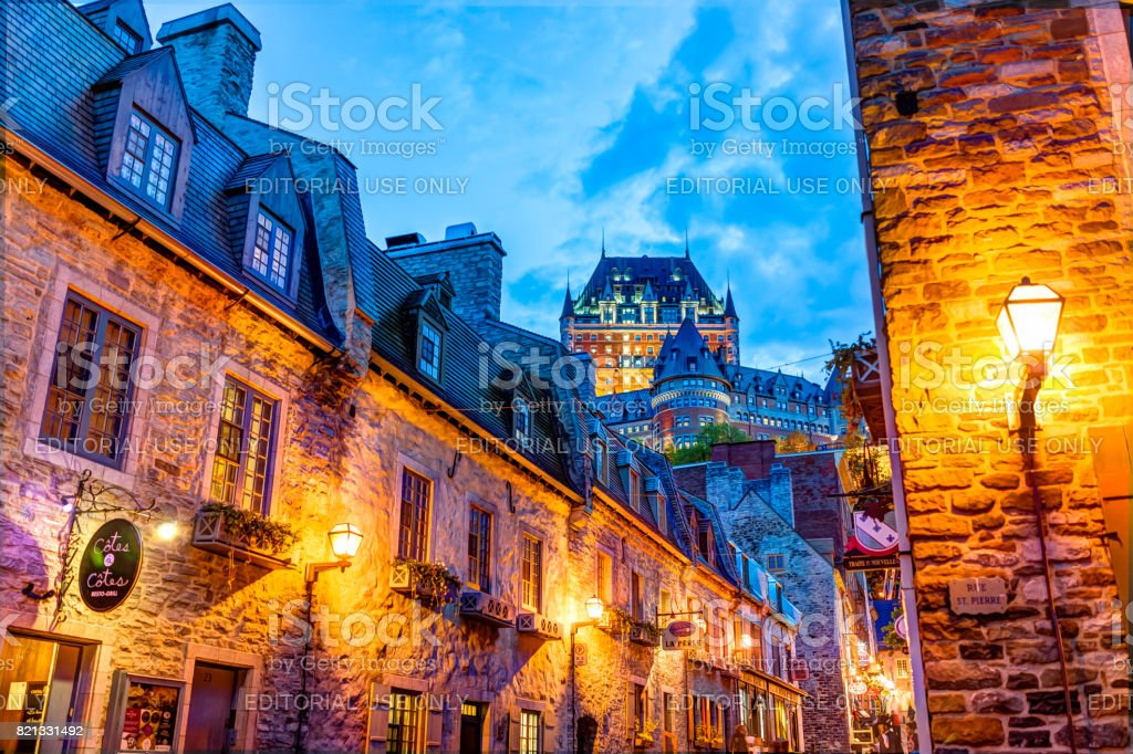 Colorful lower old town cobblestone street with stone wall buildings and view of Chateau Frontenac stock photo