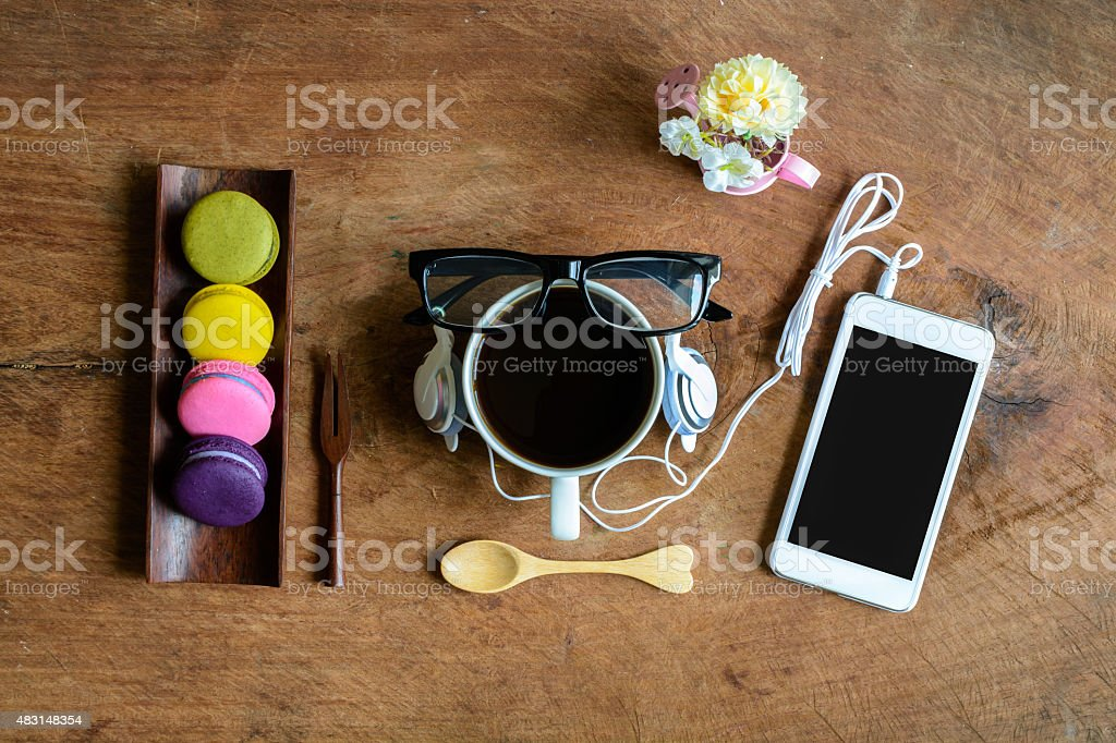 Colorful macaroons and a cup of coffee with cellphone stock photo
