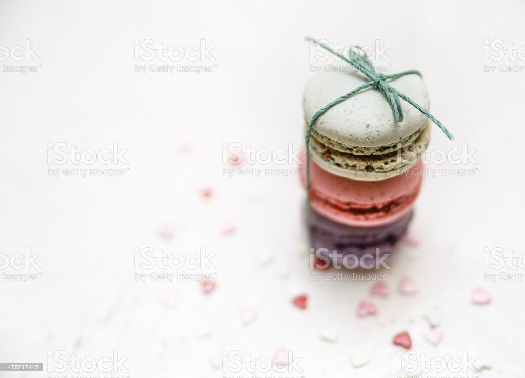 Colorful macaroons with small heart shape candies on white background stock photo