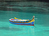 Colorful Maltese fisherman's boat 'Iuzzu' in crystal clear water