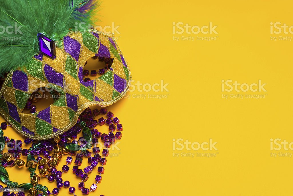 Colorful Mardi Gras or venetian mask on a yellow stock photo