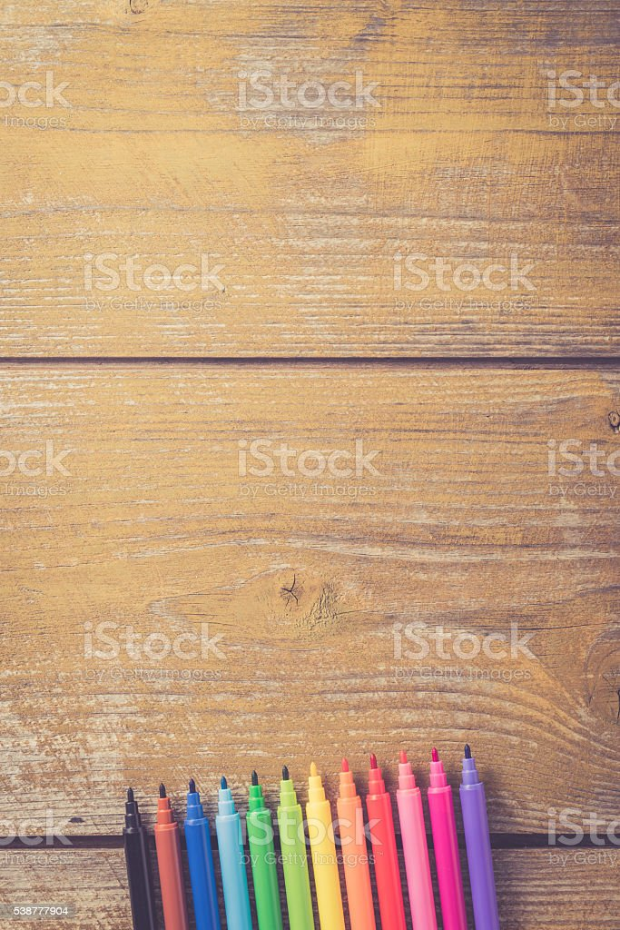 Colorful markers on yellow wooden table stock photo