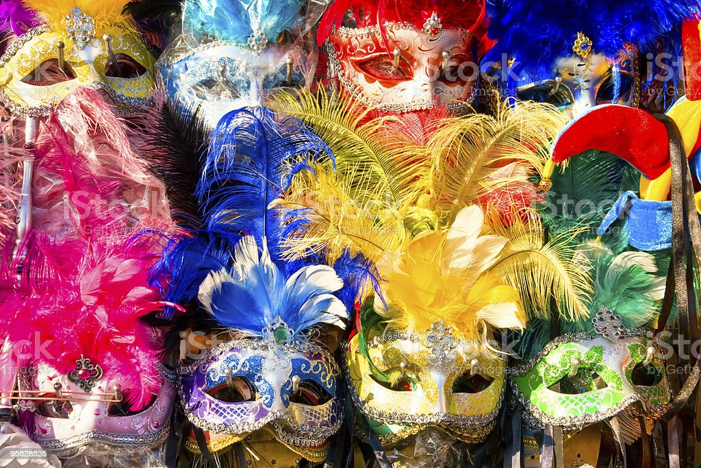 Colorful masks with glitter and feathers on display stock photo