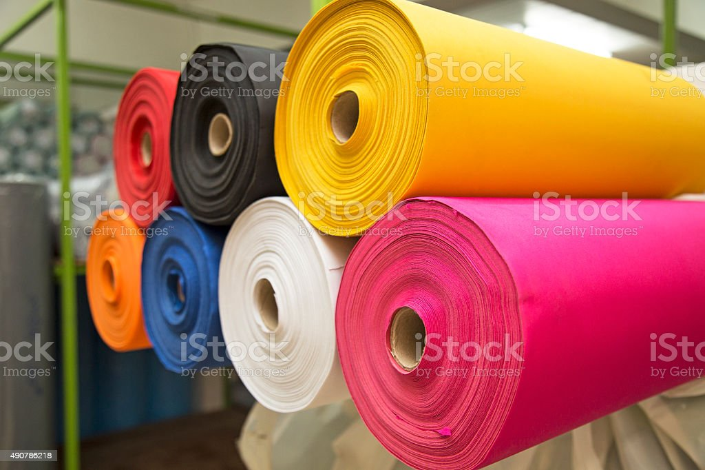 Colorful material fabric rolls in warehouse stock photo