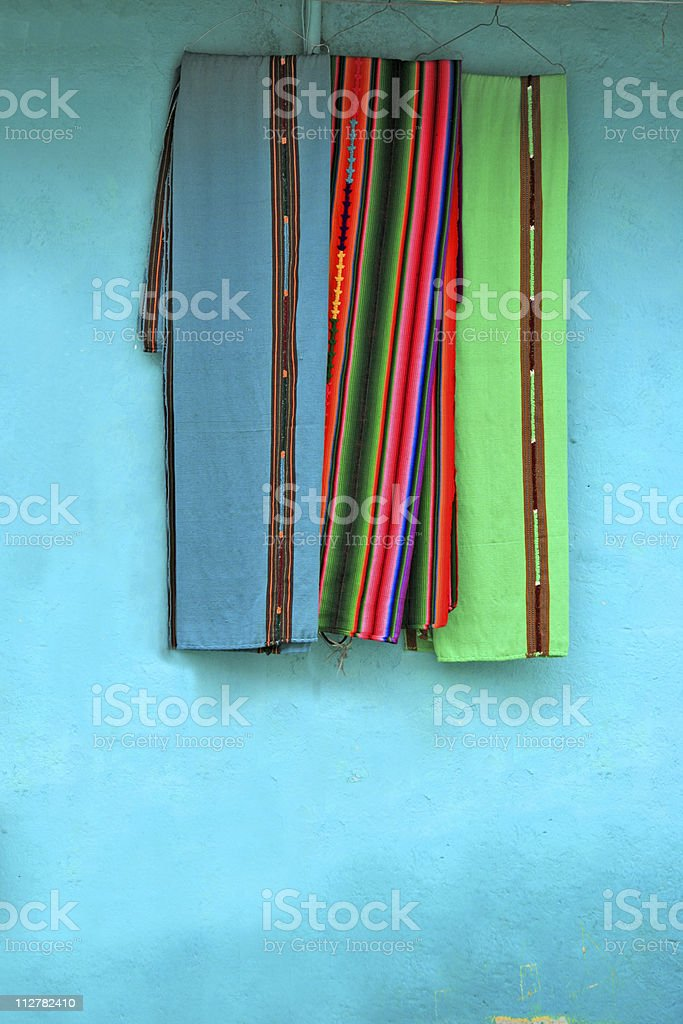 Colorful Mayan fabric hanging outsite shop in Flores, Guatemala royalty-free stock photo