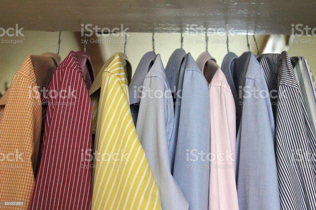Colorful men's shirts hanging in wardrobe stock photo