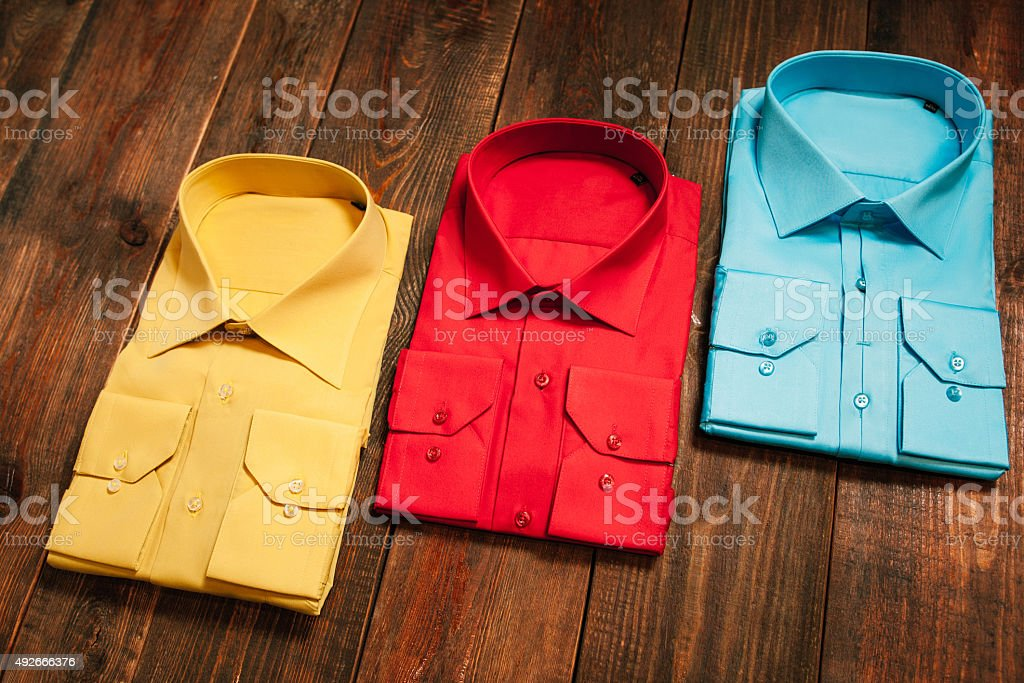 colorful men's shirts on a wooden background stock photo