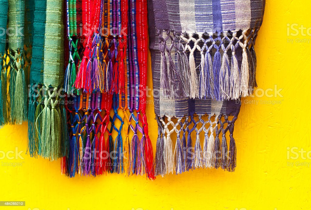 Colorful Mexican Scarves Hanging Against Vibrant Yellow Background stock photo