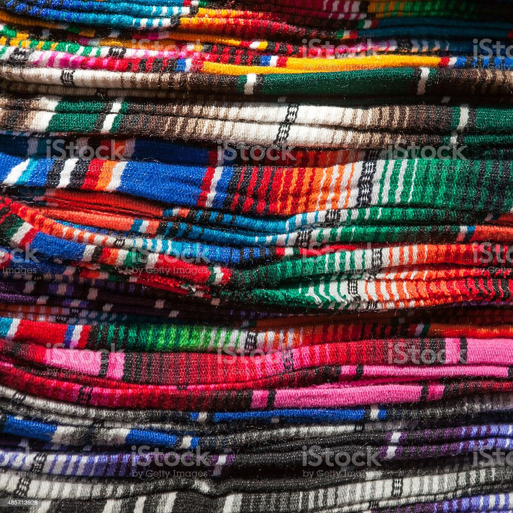 Colorful Mexican serapes hang in row stock photo