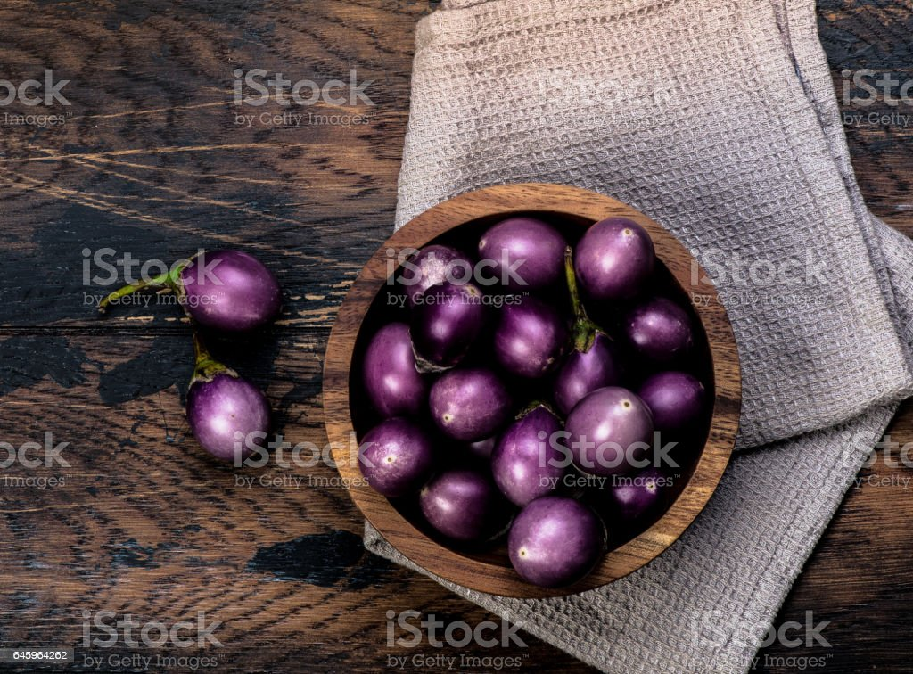 Colorful mini-eggplants on rustic wooden board. Organic raw baby Indian eggplants in a bowl. Top view. stock photo
