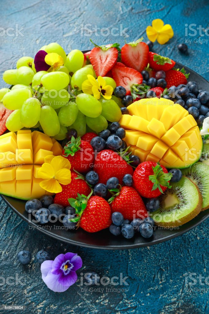 Colorful Mixed Fruit platter with Mango, Strawberry, Blueberry, Kiwi and Green Grape. Healthy food stock photo