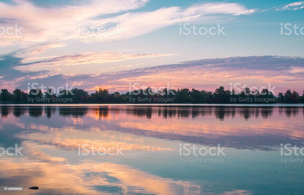 Colorful morning sunrise reflecting in clear lake waters stock photo