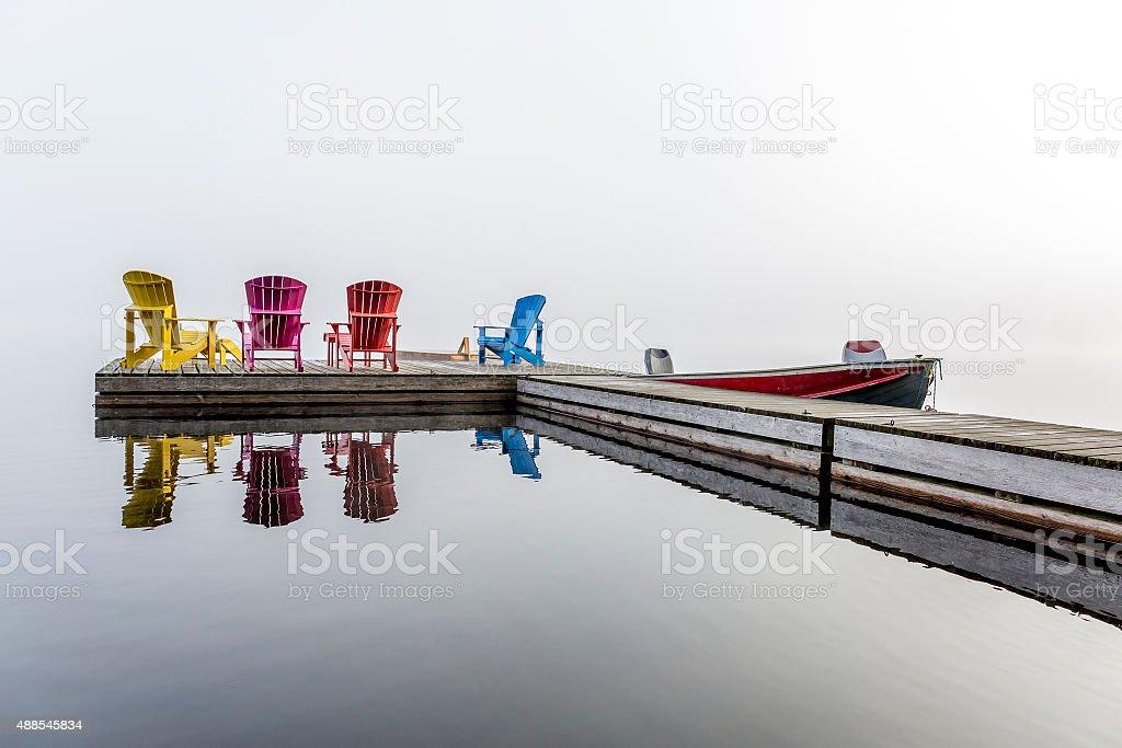 Colorful Muskoka Chairs on a Dock stock photo