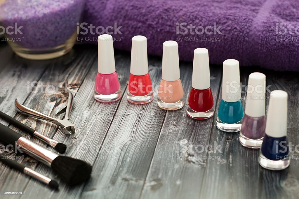 Colorful nail polish and make up brushes on wooden table stock photo