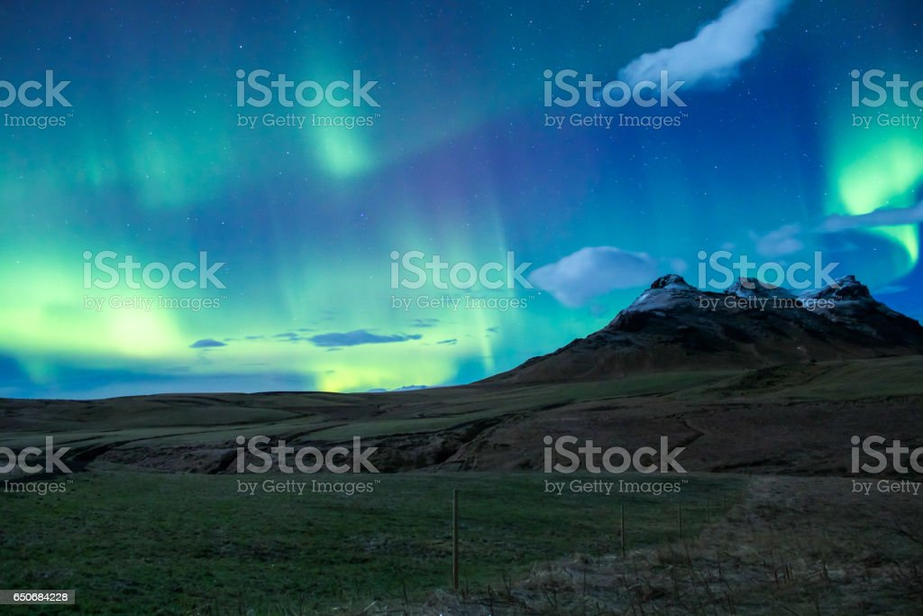 Colorful northern lights over golden fields and snowed mountains stock photo