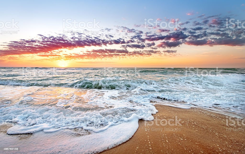 Colorful ocean beach sunrise with deep blue sky. stock photo