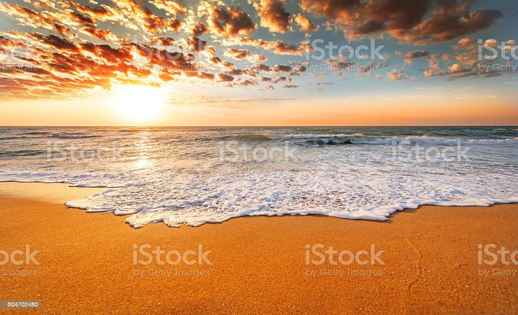 Colorful ocean beach sunrise with deep blue sky. stock photo