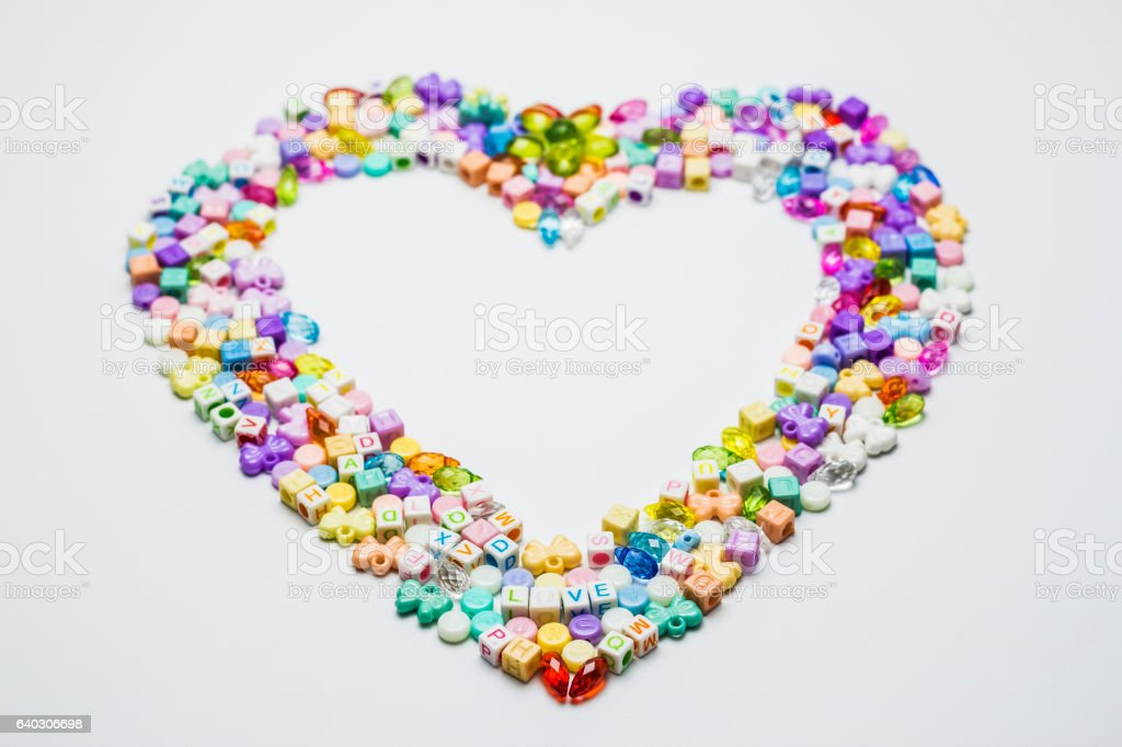 Colorful of beads with heart shape on white background. stock photo