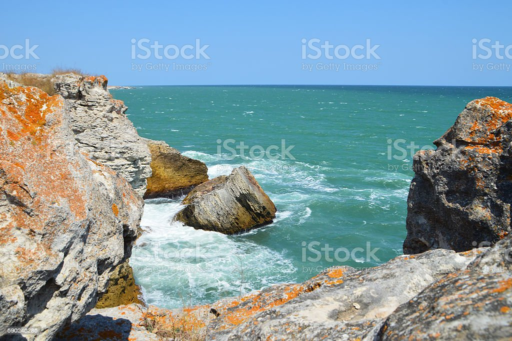 Colorful orange clifs, rocks and green sea stock photo
