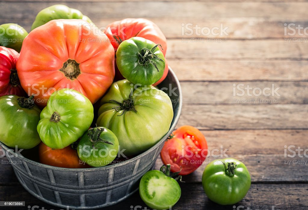 Colorful organic tomatoes on wooden table stock photo