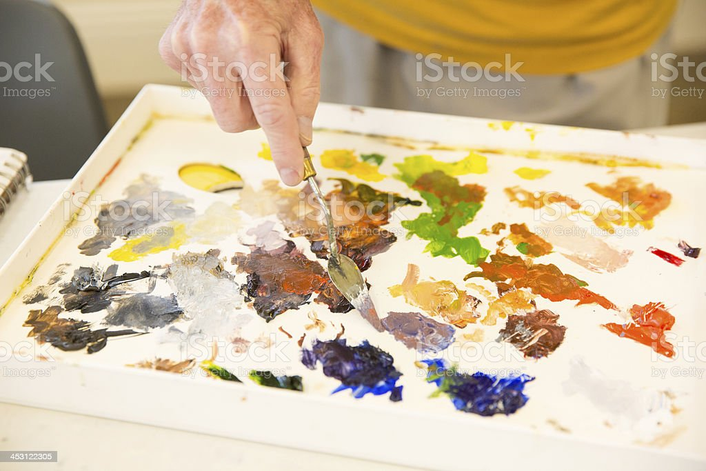 Colorful paint pallet with white male hand. royalty-free stock photo