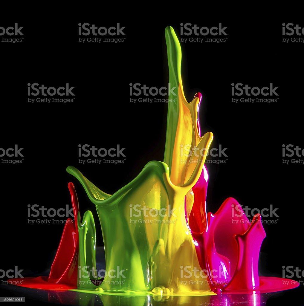 Colorful paint splashing isolated on black stock photo
