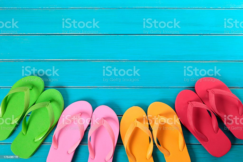 Colorful pairs of flip flops against blue wooden deck royalty-free stock photo
