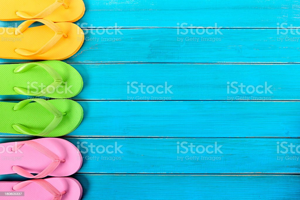 Colorful pairs of flip flops lined up on a blue wooden deck stock photo
