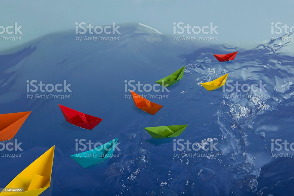 Colorful paper boats in blue water royalty-free stock photo