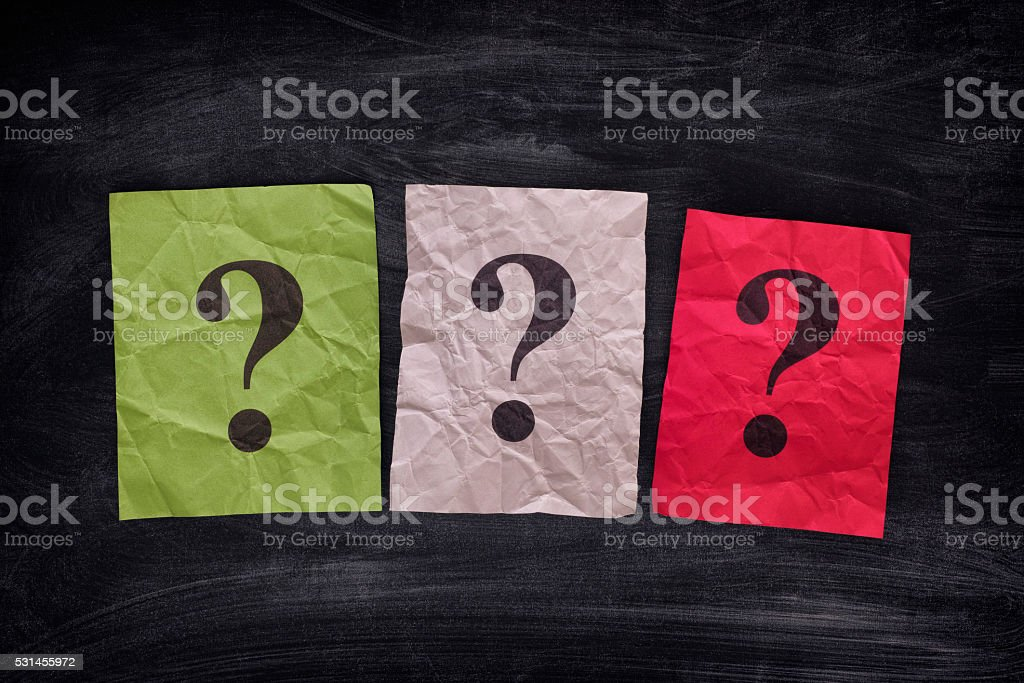 Colorful paper notes with question marks on black board stock photo
