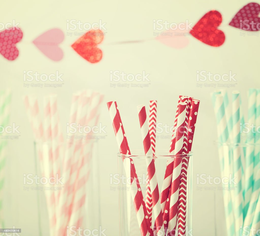 Colorful paper straws with a garland of hearts stock photo