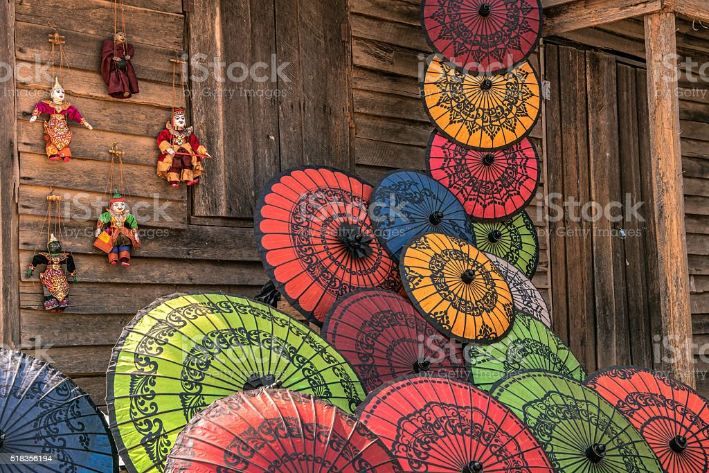 Colorful paper umbrellas on a wooden wall stock photo