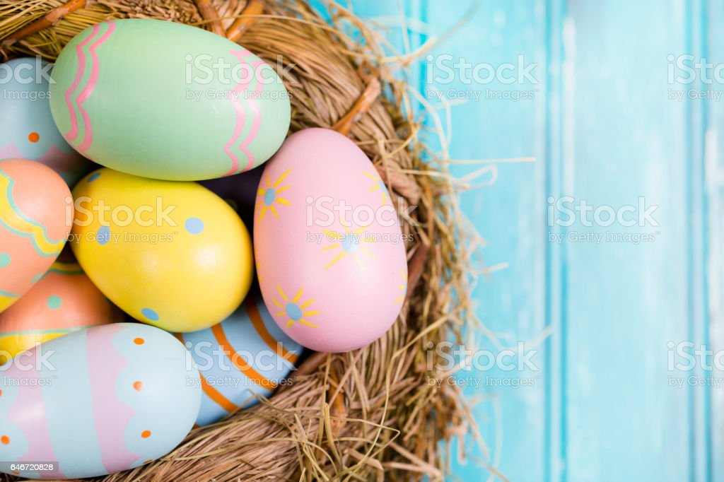 Colorful pastel Easter eggs in basket with copyspace. stock photo