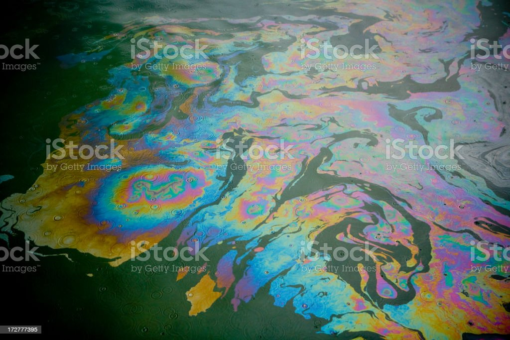 Colorful patterns in an oil slick on water stock photo