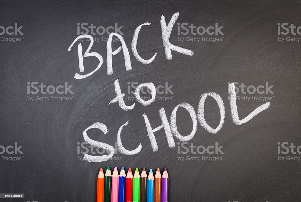 Colorful pencil crayons on a blackboard, Back to school stock photo