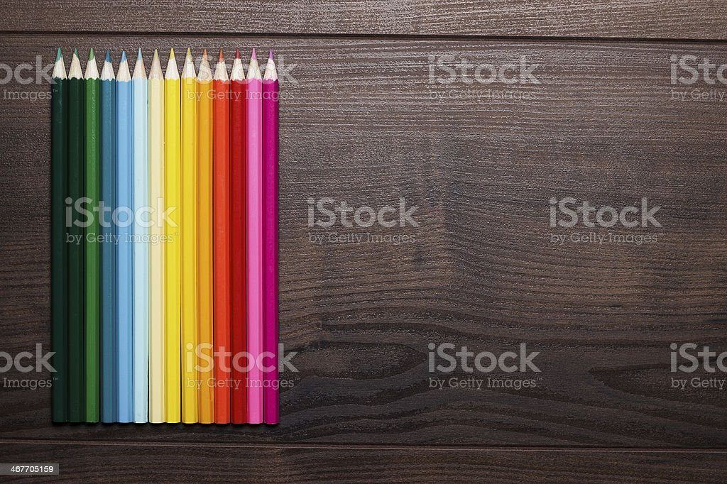 colorful pencils over brown wooden table background stock photo