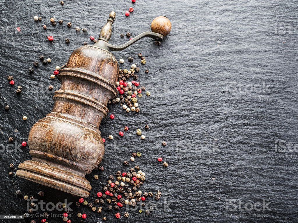 Colorful peppercorns and old pepper mill. stock photo