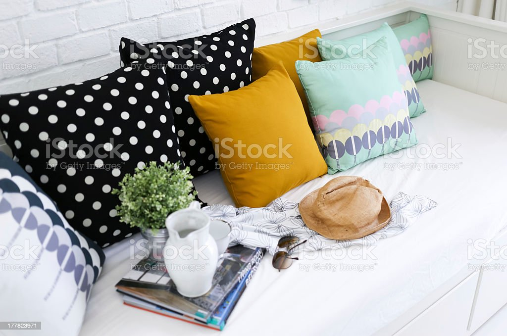 Colorful pillows, magazines, and a hat on a white sofa stock photo