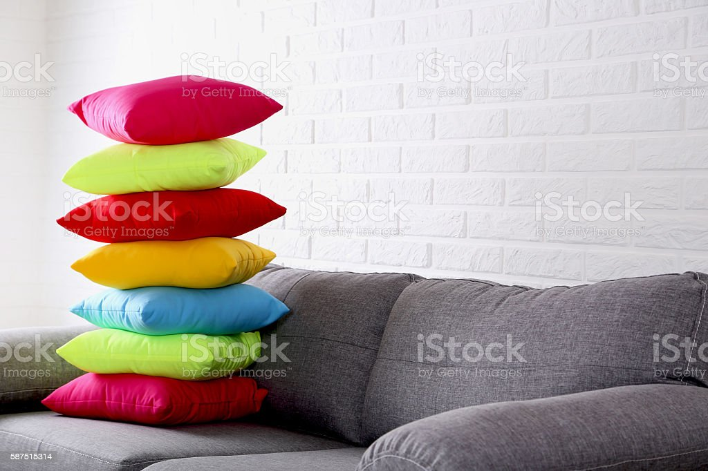 Colorful pillows on grey sofa on a brick wall background stock photo